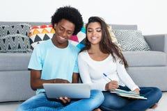 Étudiant d'afro-américain apprenant avec l'amie latine Images libres de droits