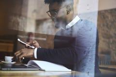 Étudiant d'afro-américain d'école de commerce dans le chandail foncé et la chemise blanche reparing pour l'examen important de la Image stock