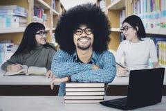 Étudiant d'Afro avec ses amis dans la bibliothèque Image libre de droits