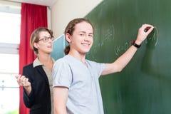 Étudiant d'essai de professeur pendant les leçons de maths à l'école Images libres de droits