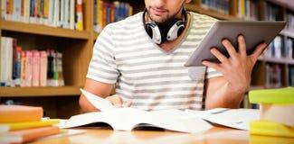 Étudiant étudiant dans la bibliothèque avec le comprimé images stock