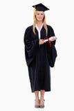 Étudiant dans la fixation graduée de robe longue son diplôme Photographie stock libre de droits