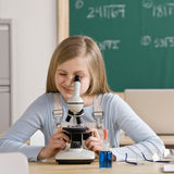 Étudiant dans la salle de classe scrutant dans le microscope Photos libres de droits