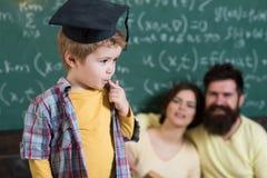 Étudiant dans le chapeau d'obtention du diplôme Petit étudiant perdu dans les pensées Garçon d'étudiant consacré à l'éducation Il Images stock