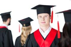 Étudiant dans le chapeau d'obtention du diplôme avec le diplôme, avec des amis derrière d'isolement sur le blanc Images libres de droits
