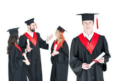 Étudiant dans le chapeau d'obtention du diplôme avec le diplôme et les amis se tenant derrière d'isolement sur le blanc Image libre de droits