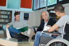 Étudiant dans le fauteuil roulant dactylographiant sur l'ordinateur portable dans la bibliothèque photos libres de droits