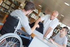 Étudiant dans le fauteuil roulant dans la bibliothèque photos stock