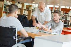 Étudiant dans le fauteuil roulant parlant au professeur et à l'étudiant photo libre de droits