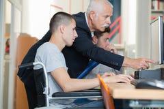 Étudiant dans le fauteuil roulant parlant avec le camarade de classe dans la bibliothèque Photo libre de droits