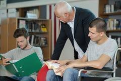 Étudiant dans le fauteuil roulant parlant avec le camarade de classe dans la bibliothèque Images stock