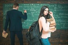 Étudiant de brune avec le tas des livres et du sac à dos lourd tenant ses verres Étudiante se tenant devant le vert photos libres de droits
