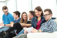 Étudiant de fille avec des amis s'asseyant dans le lobby et merci Photos libres de droits
