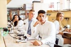 Étudiant de lycée avec des microscopes dans le laboratoire Photos libres de droits
