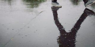 Étudiant de marche dans un campus réflexion Jour pluvieux Photo libre de droits