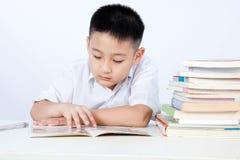 Étudiant de port Uniform Reading Textboo de Little Boy de Chinois asiatique images stock