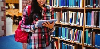 Étudiant de sourire à l'aide du comprimé dans la bibliothèque images libres de droits