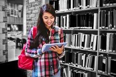 Étudiant de sourire à l'aide du comprimé dans la bibliothèque photo stock