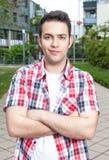 Étudiant de sourire avec la chemise vérifiée et les bras croisés Photo stock