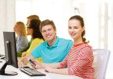 Étudiant de sourire avec le smartphone dans la classe d'ordinateur Photographie stock libre de droits
