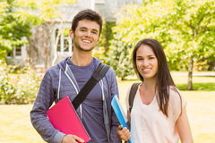 Étudiant de sourire d'amis se tenant avec le sac d'épaule tenant le livre Image libre de droits