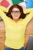 Étudiant de sourire dans des lunettes se trouvant sur le plancher Photographie stock libre de droits