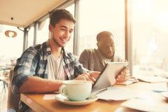 Étudiant de sourire positif se reposant dans le cafétéria Photographie stock libre de droits