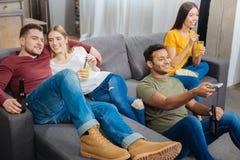 Étudiant de sourire regardant l'ami tout en regardant la TV avec lui et des amis Photographie stock