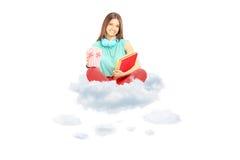 Étudiant de sourire s'asseyant sur un nuage avec les carnets et le maïs éclaté b Images stock