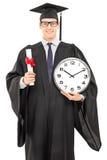 Étudiant de troisième cycle masculin tenant un diplôme et une grande horloge murale Photo stock