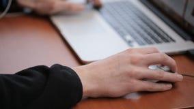 Étudiant de troisième cycle recherchant l'information sur l'Internet utilisant un ordinateur portable et une souris d'ordinateur banque de vidéos
