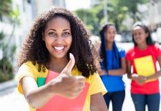 Étudiant des Caraïbes montrant le pouce dans la ville avec des amis Images stock