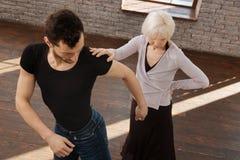 Étudiant en dernière année de enseignement de divan utile de danse dans la salle de bal Image stock