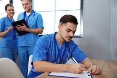 Étudiant en médecine avec des groupmates étudiant dans la bibliothèque photographie stock libre de droits
