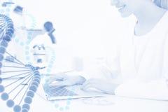 Étudiant en médecine travaillant avec l'ordinateur portable dans le laboratoire scientifique moderne et le brin graphique d'ADN photos stock