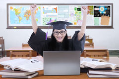 Étudiant enthousiaste avec la robe d'obtention du diplôme dans la classe Photo stock