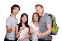 Étudiant et pouce heureux de groupe d'amis  Images stock