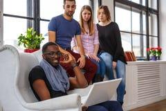 Étudiant ethnique multi à l'aide de l'ordinateur portable Photographie stock