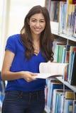Étudiant féminin étudiant dans la bibliothèque image stock