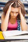 Étudiant féminin chargé dans une bibliothèque Photo stock