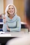 Étudiant féminin mûr soulevant la main dans la classe Image stock