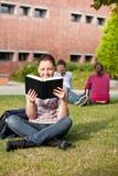 Étudiant féminin sérieux affichant un livre sur l'herbe Photographie stock