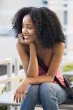 Étudiant féminin s'asseyant à l'extérieur Photographie stock libre de droits