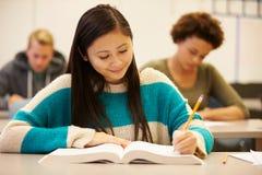 Étudiant féminin Studying At Desk de lycée dans la salle de classe Photographie stock