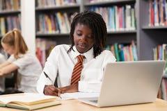 Étudiant féminin Wearing Uniform Working de lycée à l'ordinateur portable dedans image stock