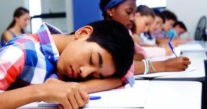 Étudiant fatigué dormant dans la salle de classe clips vidéos