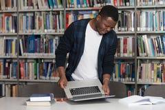 Étudiant frustrant Throwing His Laptop Photo stock