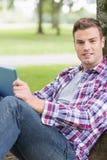 Étudiant gai à l'aide de son PC de comprimé en dehors du penchement sur l'arbre Photographie stock
