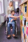 Étudiant handicapé de sourire avec le camarade de classe dans la bibliothèque images libres de droits