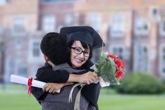 Étudiant heureux étreignant l'ami sur l'obtention du diplôme à l'école Photos stock